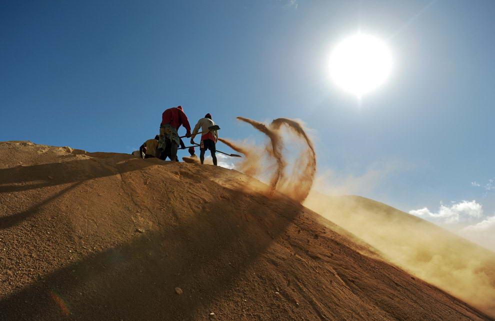 руппа рабочих за подённую оплату копают песок и рыхлый грунт на сапфировом карьере