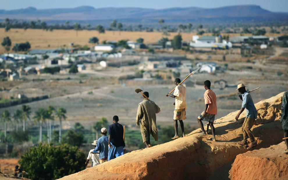 Старатели заканчивают смену и возвращаются из шахты к своим семьям в поселок Илакака (виден на заднем плане).