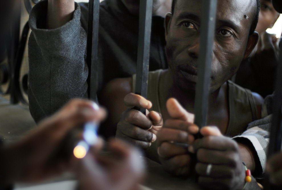 Местный старатель вместе с другими работниками ждёт у окна ювелирной мастерской в Илакаке с надеждой, что покупатель со Шри-Ланки, который заинтересовался его камнями, захочет купить их.