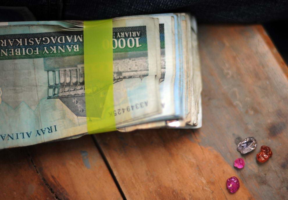 Четыре сапфира рядом с пачкой банкнот в ювелирной мастерской, где покупатель драгоценных камней со Шри-Ланки оценивает сапфиры,