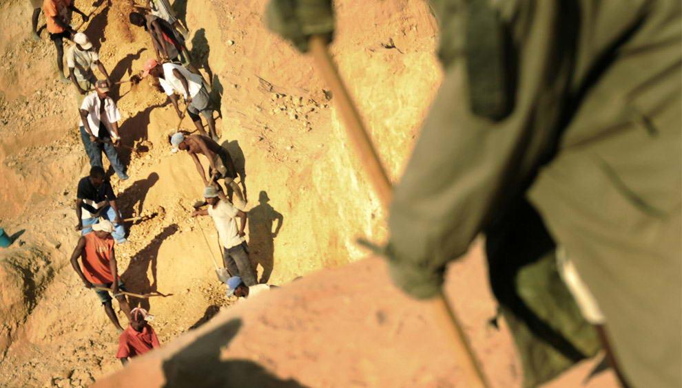 Группа старателей раскапывает гравий и песок на вершине холма около сапфировой шахты