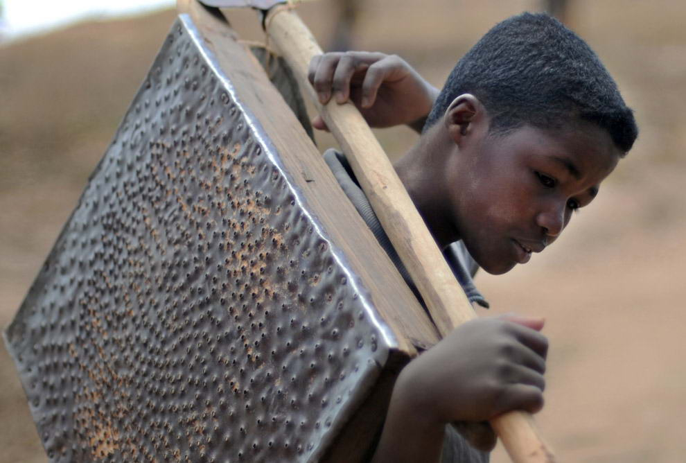 10-ти летний Франсуа Рантонирина несет лопату и самодельное сито, с помощью которых они с матерью в поисках сапфиров все утро просеивали гравий