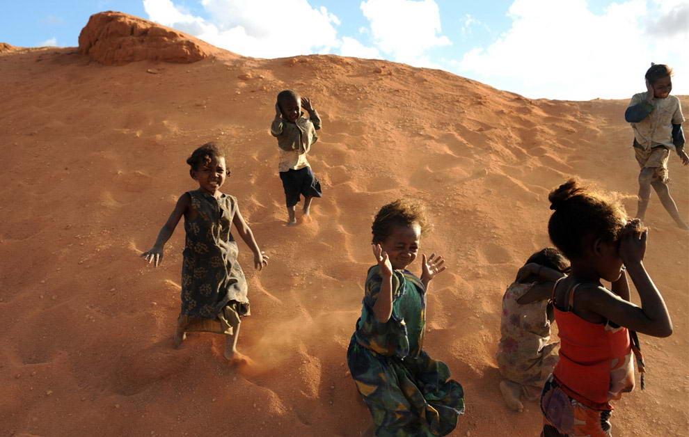 Ветер несет песок из сапфировой шахты в сторону детей, которые играют неподалеку от шахты