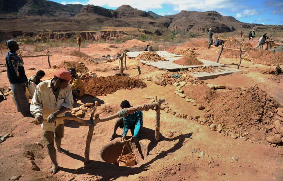 Два старателя аккуратно извлекают сумку с гравием из глубин шахты возле реки, где они с остальными работниками ищут сапфиры