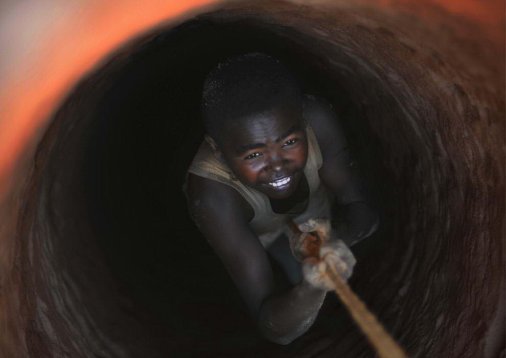 Юный старатель крепко держится за веревку, которую опускают в глубокое отверстие в земле