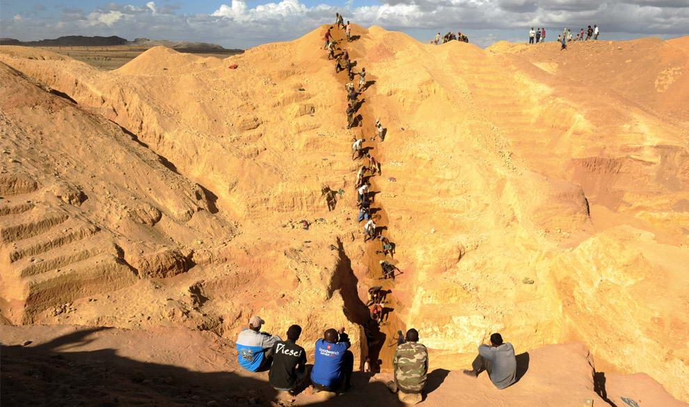 Пятеро мужчин наблюдают за группой старателей, которые достают гравий и песок из большой сапфировой шахты