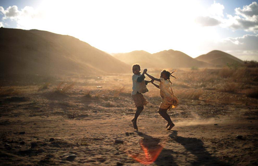 Мандраисара (справа) и ее подруга Тафитасоаниана (слева) возле гор песка и гравия танцуют и поют под песню, которую они услышали по местной популярной радиостанции.