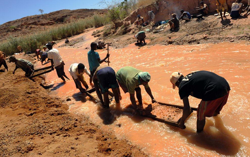 Старатели промывают гравий на ситах в реке в поисках сапфиров в Анзанакаро