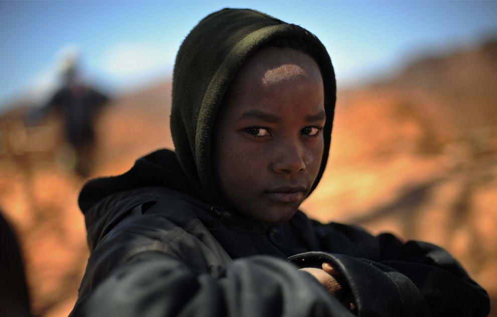 13-ти летний Донне сидит около своего отца, пока тот готовит кофе во время перерыва от добычи сапфиров в Анзанакаро на Мадагаскаре.