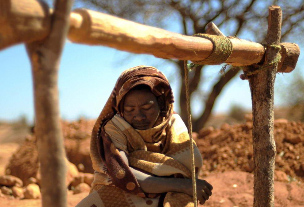 Женщина- старатель терпеливо ждет, пока ее напарник затянет веревку внутрь глубокой шахты