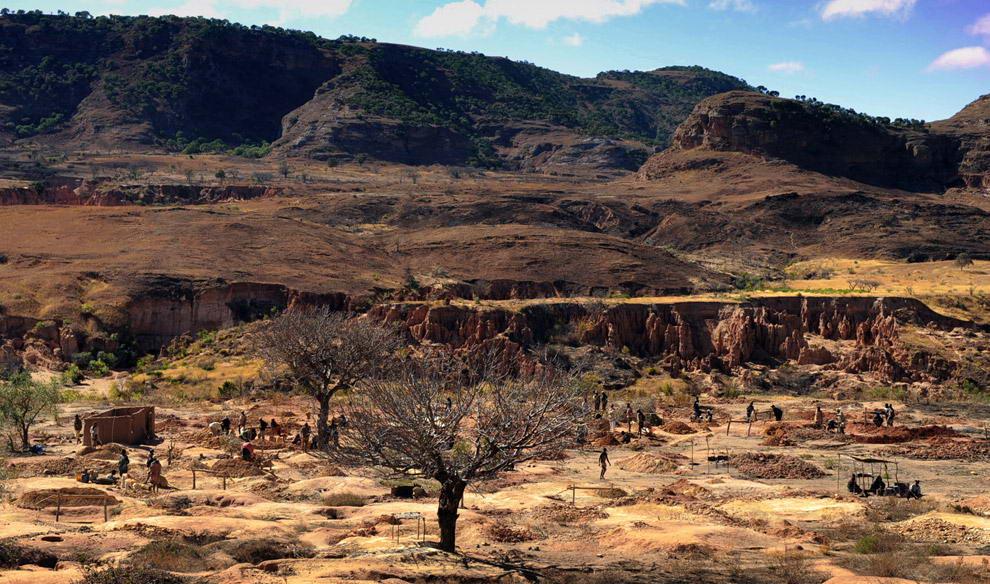 Старатели работают на изрытой ямами территории месторождения, занимаясь поисками сапфиров возле реки