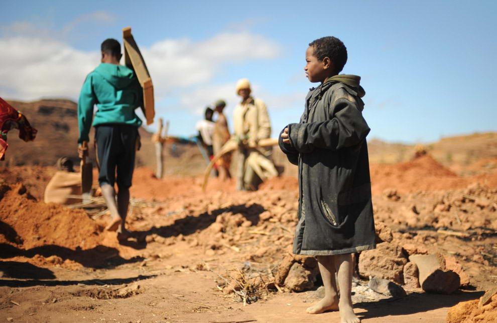 13-ти летний Донне наблюдает за взрослыми старателями, которые направляются к реке для промывки гравия