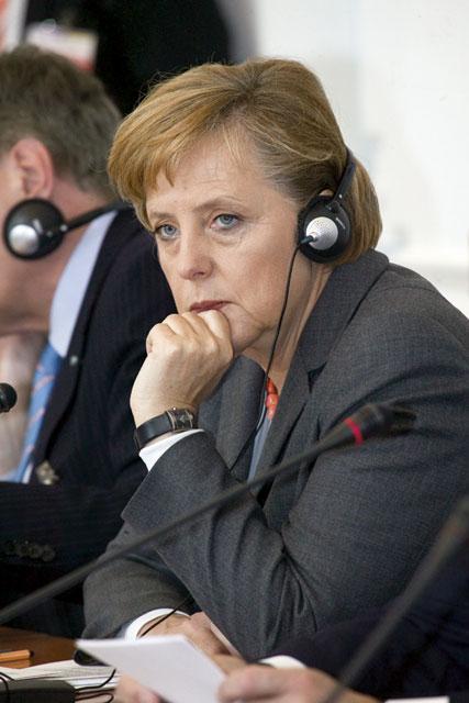 Ангела Меркель, поглаживая подбородок, пытается принять решение.