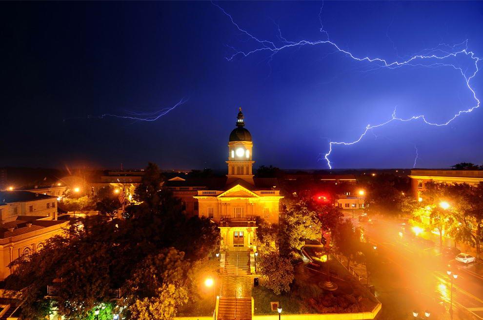 Молния освещает небо позади здания мэрии в городе Афины, штат Джорджия рано утром, 18 июня 2009. Более 4000 человек остались без света в Северо-Восточной Джорджии во время этой грозы. (AP Photo/The Athens Banner-Herald, Kelly Lambert)