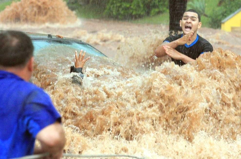 Автомобилисты во время наводнения, причиной которых стали сильные дожди. Снимок сделан в Сан-Жозе-ду-Риу-Прету, Бразилия.