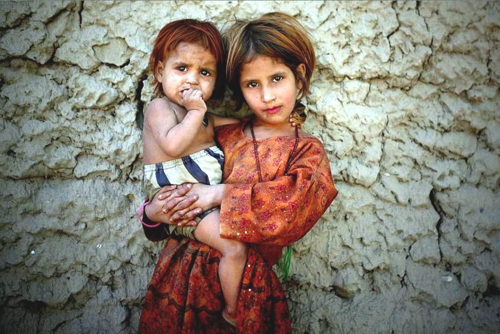 Зубайда, афганская девочка, держит свою младшую сестренку, позируя фотографу в Джелалабаде, провинция Нангархар, к востоку от Кабула.